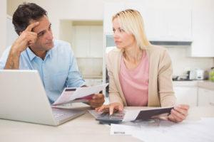 Eine skeptische Frau und ihr Mann analysieren Unterlagen und nutzen dazu einen Taschenrechner und einen Laptop