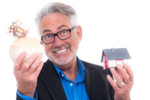 Ein lachender Mann mit Bart hält ein gefülltes Sparschwein und ein Spielzeughäuschen