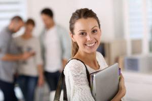 Eine lächelnde Studentin steht mir Ihren Büchern vor der Brust auf dem Gang einer Hochschule