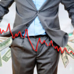 Mann in Businesskleidung zeigt leere Hosentaschen. Im Vordergrund fliegende Geldscheine und ein Liniendiagramm