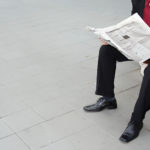 Mann in Anzug liest Zeitung auf einer Bank