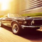 Lila Ford Mustang im Sonnenuntergang in Bewegung