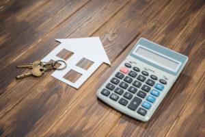 Ein Hausschlüssel liegt auf einem Papierumriss eines Haus, daneben ein Taschenrechner