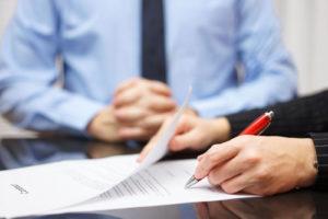 Jemand unterzeichnet einen Vertrag, ein Mann mit Hemd und Krawatte sitzt mit gefalteten Händen dabei