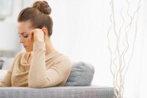 Eine ärgerliche Frau sitzt auf einer Couch