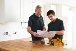 Zwei Monteure in einer neuen Küche mit Bauplan in der Hand