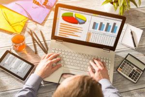 Ein Mann sitzt vor einem Laptop der Diagramme und Daten zeigt
